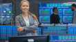 Successful Female Stock Trader Crosses Arms and Smiles at the Camera. In the Background Busy Stock Exchange Office with Traders, Brokers and Dealers Selling and Buying Bonds. Displays Show Numbers.
