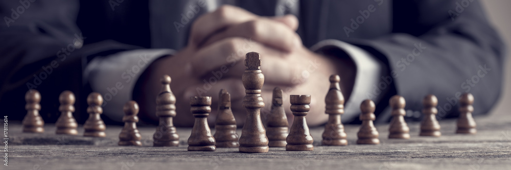 Fototapeta Retro style image of a businessman with clasped hands planning strategy with chess figures