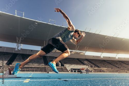 Sprinter taking off from starting block on running track Fototapete