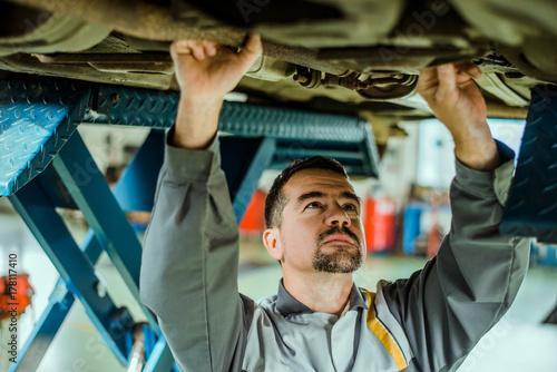 Zdjęcie XXL Profesjonalny mechanik naprawiający samochód.