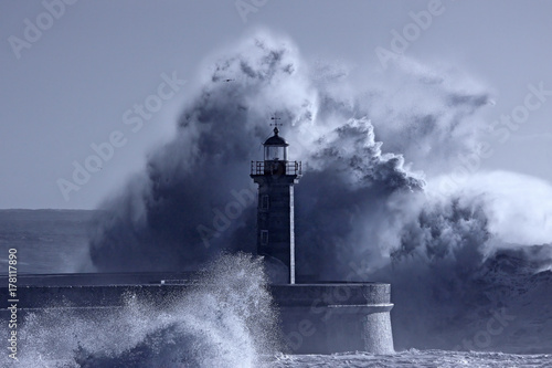 Stickers pour porte Eau Lighthouse in the middle of stormy waves