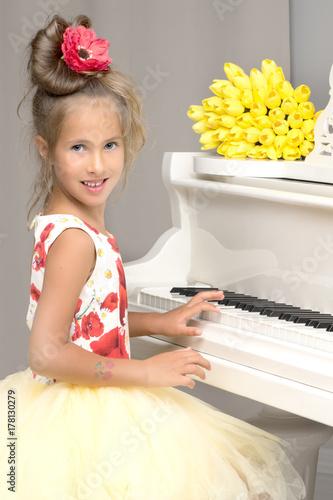 Plakat Piękna mała dziewczynka gra na białym fortepianie.