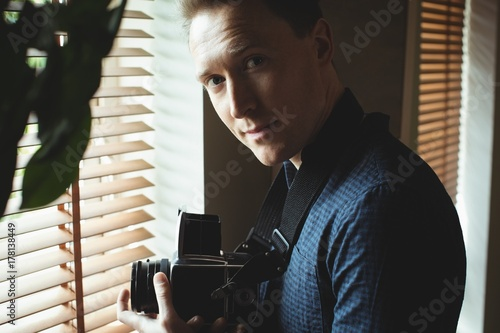 Tuinposter Retro Handsome man holding vintage camera near window