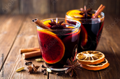 Fotomural Two glasses of christmas mulled wine with oranges and spices on wooden background