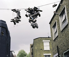 Old Sports Shoes Hanging From A Telephone Wire In London