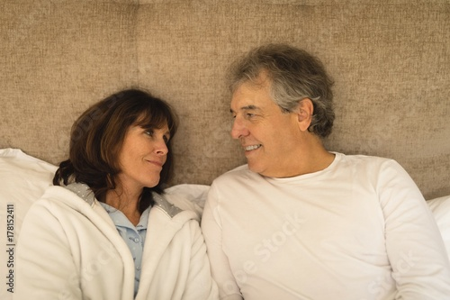 Happy senior couple smiling in bed