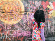 African-American Girl Doodling With Chalk On A Blackboard