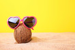 Leinwandbild Motiv Coconut with sunglasses on the beach sand