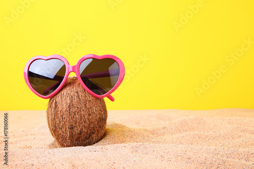Coconut with sunglasses on the beach sand