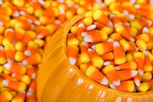 Ceramic Decorative Pumpkin Filled With Halloween Candy Corn. Closeup With Candy Corn Background.