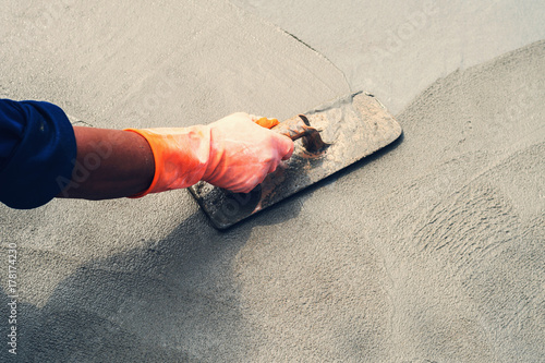 Fotografía  close up hand worker leveling concrete pavement for mix cement at construction s