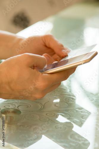 Zdjęcie XXL Internetowa bankowość w żeńskich rękach przeciw tłu szklany stół