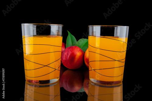 Fototapeta Brzoskwinia sok w szkłach na czarnym tła zakończeniu up