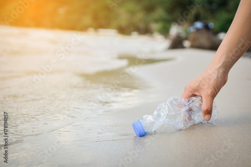 Valokuvatapetti Hand woman picking up plastic bottle cleaning on the beach , volunteer concept