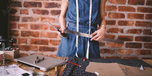 Young female fashion designer holding tools in her hands