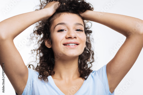 Close up of curly woman lifting up her hair Wallpaper Mural