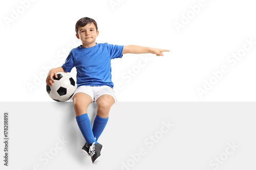 Juliste  Little footballer sitting on a panel and pointing