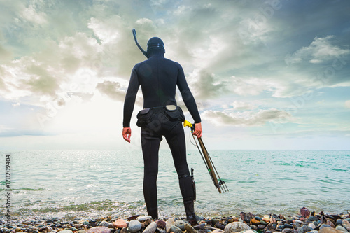 Underwater hunter on the beach preparing to dive. Underwater fishing concept. Back view.