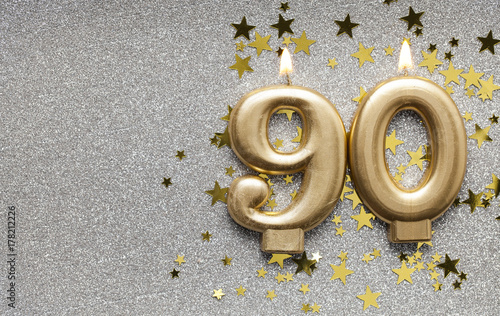 Fotografia  Number 90 gold celebration candle on star and glitter background