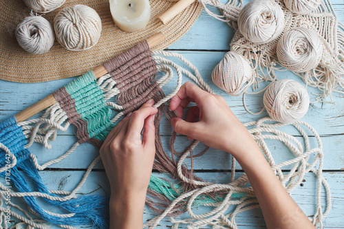 Foto  Hobby knitting macrame top view of the hand and thread on a wooden Board