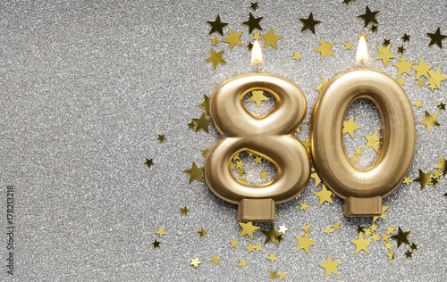 Fotografia  Number 80 gold celebration candle on star and glitter background