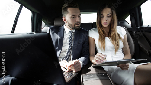 man and woman discussing work documents in taxi Tableau sur Toile