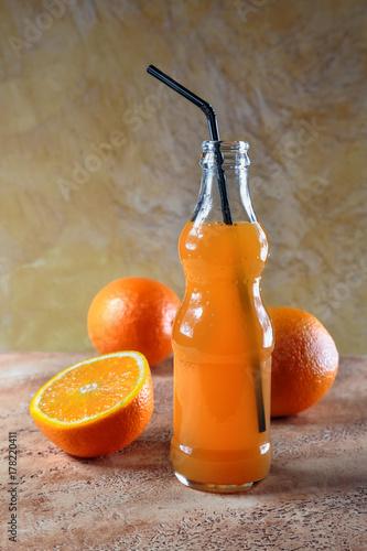Fototapeta świeżo wyciśnięty sok pomarańczowy w małej butelce ze słomką na tle soczystych pomarańczy