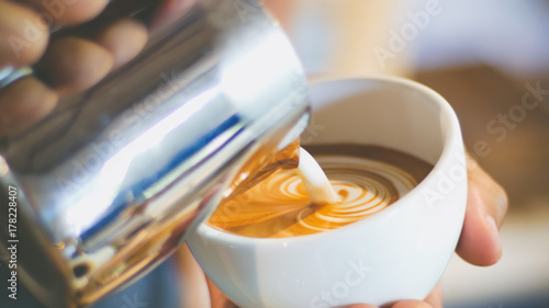 Foto barista pouring streamed milk to make heart shape latte art in cup of hot coffee