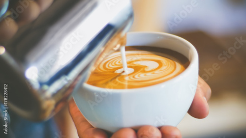 barista pouring streamed milk to make heart shape latte art in cup of hot coffee Fototapete