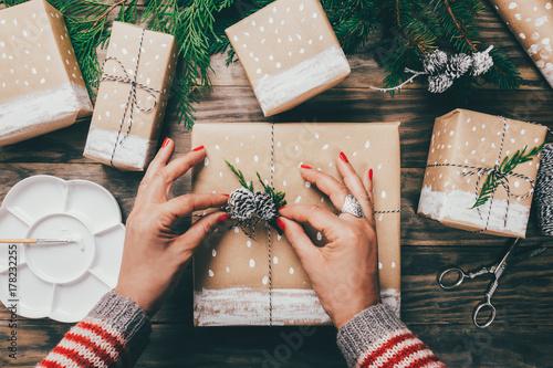 Fotografía  Woman wrapping Christmas presents in a crafty way