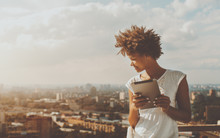 Cheerful Young Black Curly Female Leaning On Railing Of Balcony Of Skyscraper, Holding Digital Tablet And Looking Down On City From High Above; With Copy Space Place For Text, Your Message Or Advert