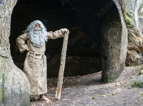 Leinwand Poster bearded hermit in a cave stands with stick in hand
