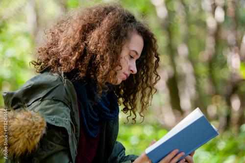 Plakat Nastoletniej dziewczyny czytelnicza książka w jesień parku