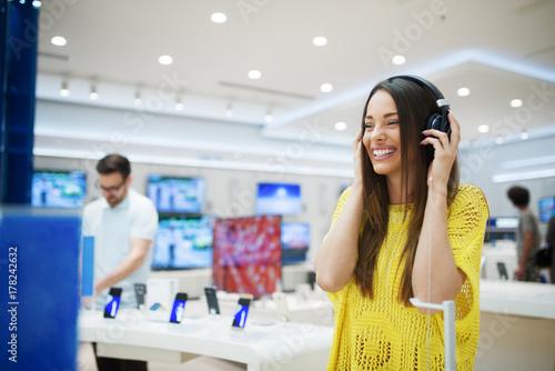 Plakat Wspaniała szczęśliwa dziewczyna bada hełmofony w technika sklepie.