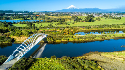 Aerial view on a beautiful bridge across a small stream with Mount Taranaki on the background. New Zealand