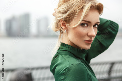 Fotografie, Tablou  Gorgeous lady in green dress poses before a river in New York