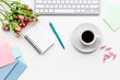 female work space with flowers, coffee and notebook white background top view mockup