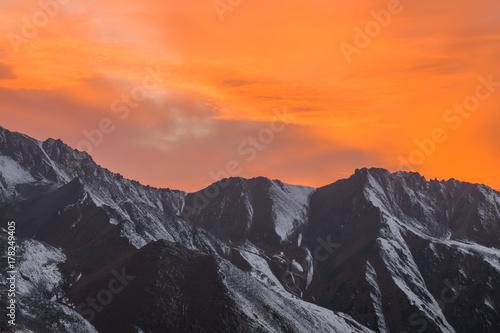 Poster Oranje eclat orange sunset over the mountain peaks