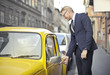 Businessman opening his vintage yellow car