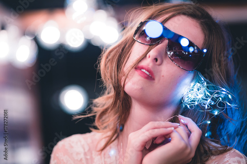 Poster Gypsy Attractive young caucasian woman poses with string lights with heavy bokeh