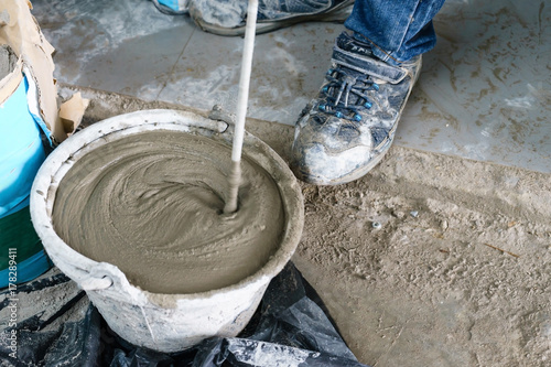 Fotografie, Obraz  Mixing cement with a mixer in a bucket on the street