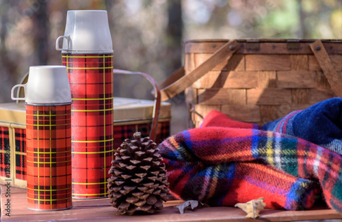 фотографія  Vintage plaid thermos and tin basket - outdoor recreation concept