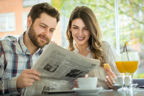 A young couple reading the newspaper