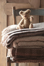 Small Teddy Bear On Chair With Wool Blankets
