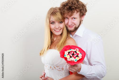 Plakat Szczęśliwa para z cukierków wiązki kwiatami. Miłość.
