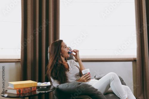 Zdjęcie XXL Piękna młoda kobieta siedzi na nowoczesne krzesło przed okna w domu, jedzenie macaroons i picia kawy lub herbaty