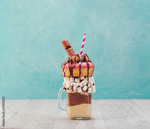 Fotografie, Obraz  Chocolate and donuts extreme milkshake with marshmallow and other sweets in mason jar on gray wooden table and blue background