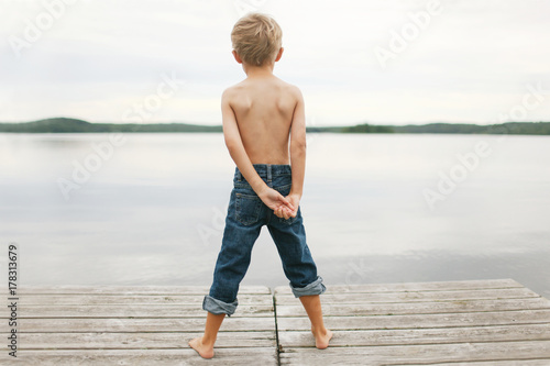 boy standing at the end of a pier