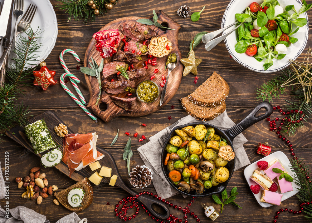 Fototapety, obrazy: Flat lay of Delicious Christmas themed dinner table with roasted meat steak, appetizers and desserts. Top view. Holiday concept.