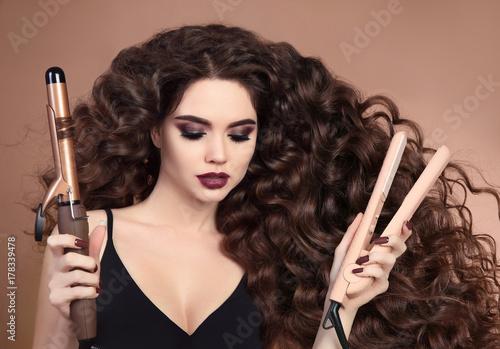 Fotodibond 3D Kręcone włosy. Piękno Zakończenie brunetki dziewczyna z podmuchowym fryzury mienia fryzowaniem i prostować żelazo. Cień do powiek Marsala. Seksowny modne kobiece kobieta na białym tle na beżowym tle.